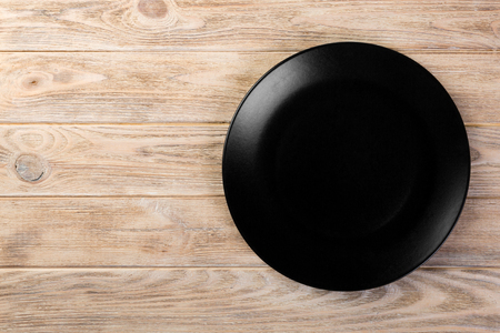 Directy above Empty black matte dish for dinner on orange wooden background with copy space.
