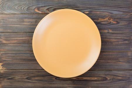 Directy above Empty orange matte plate on darkwooden background. Фото со стока