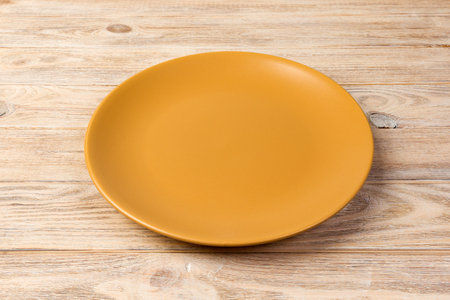 Perspective view. Empty yellow matte plate on orange wooden background. Фото со стока