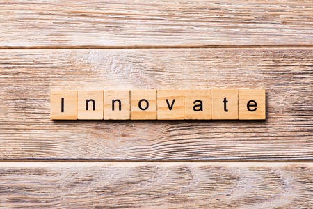 INNOVATE word written on wood block. INNOVATE text on wooden table for your desing, concept.