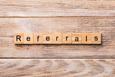 REFERRALS word written on wood block. REFERRALS text on wooden table for your desing, concept.