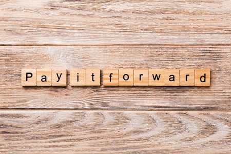 Pay It Forward word written on wood block. Pay It Forward text on wooden table for your desing, concept.