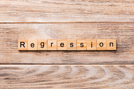 regression word written on wood block. regression text on wooden table for your desing, concept.