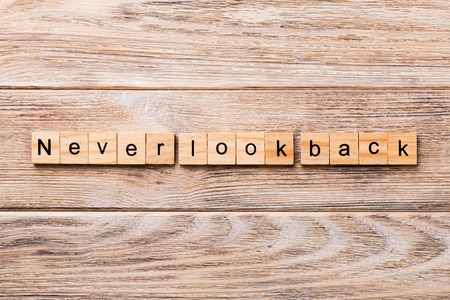 never look back word written on wood block. never look back text on wooden table for your desing, concept. Foto de archivo