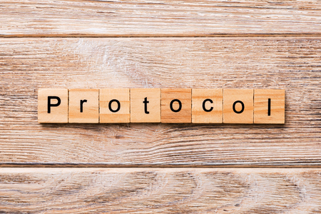 PROTOCOL word written on wood block. PROTOCOL text on wooden table for your desing, concept. Stock Photo