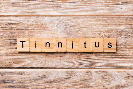 TINNITUS word written on wood block. TINNITUS text on wooden table for your desing, concept.