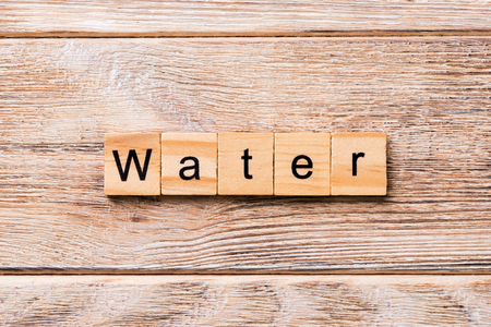 water word written on wood block. water text on wooden table for your desing, concept. Imagens