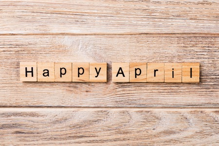 Happy april word written on wood block. Happy april text on table, concept.