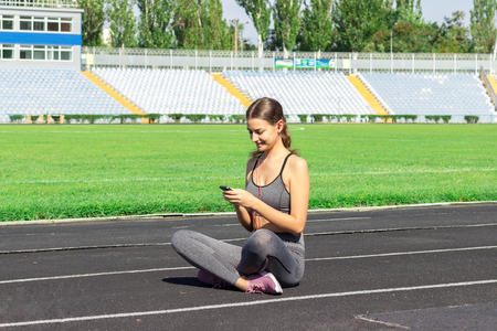 A beautiful fitness girl in grey sportswear uses smartphone and listens to music at the stadium after workout. Sports and healthy concept.