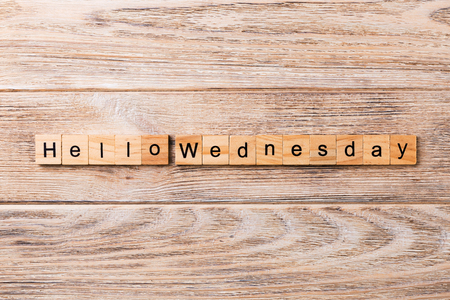 Hello wednesday word written on wood block. hello wednesday text on wooden table for your desing, concept.