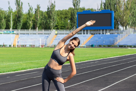 young woman warms up before jogging on stadium, People sport and fitness concept. 写真素材