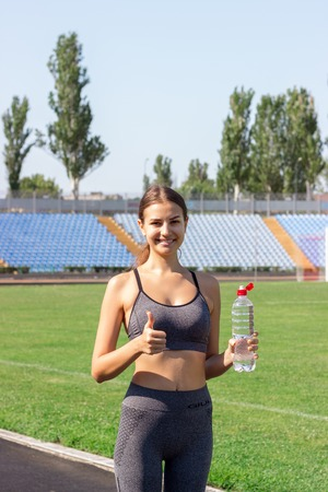 Portrait of happy female athlete holding a bottle of water and thumb up on the stadium. Sports and healthy concept.