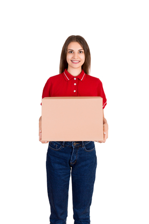 Attractive happy smiling delivery woman is holding a cardboard box isolated on white background.