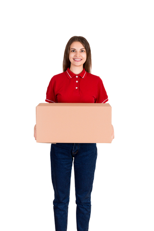 Friendly young delivey girl brings a big parcel for a customer isolated on white background.
