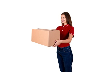 Smiling young female courier is giving a parcel box to a client isolated on white background. Banco de Imagens