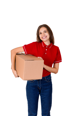 Happy young delivery girl in a red T-shirt is holding a carton parcel box under her arm isolated on white background.