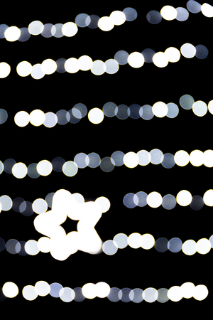 Abstract bokeh of white city lights on black background. defocused and blurred with star of light.