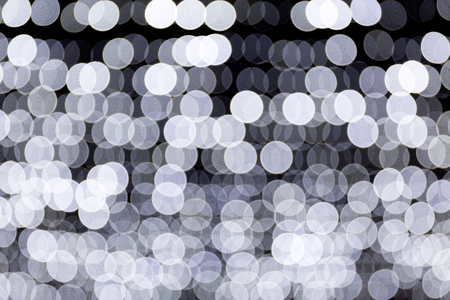 Abstract bokeh of white city lights on black background. defocused and blurred many round light.