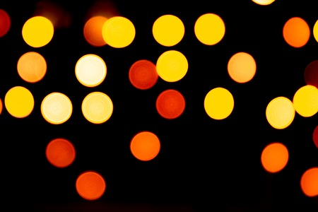Unfocused abstract gold bokeh on black background. defocused and blurred many round light.