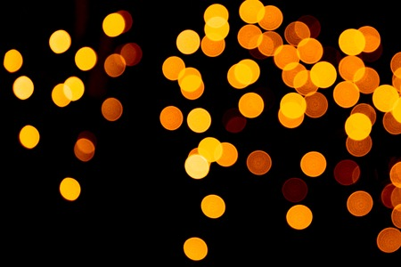 Unfocused abstract gold bokeh on black background. defocused and blurred many round light. 免版税图像