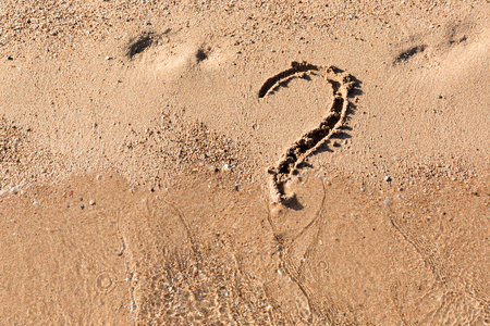 Question mark sign on sand beach near the sea. Concept of dilemma, answer and question.