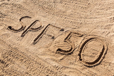 Sun protect factor fifty concept. SPF 50 word written on the beach.