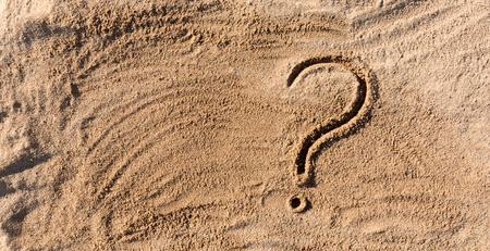 vraagtekens geschreven op strandzand close-up, met kopie ruimte.