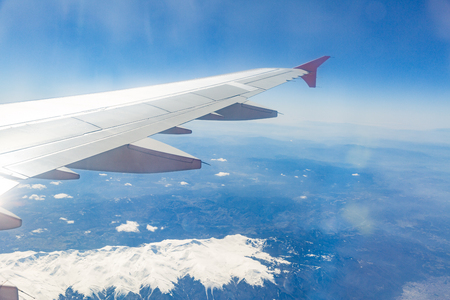 view from the window of the plane that flies over the mountains.