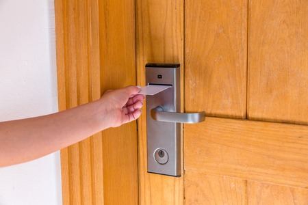 Female hand putting and holding magnetic key card switch in to open hotel room door.