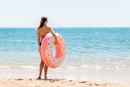 A woman walks into the sea water. Girl relaxing on inflatable ring on the beach. Summer holidays and vacation concept.