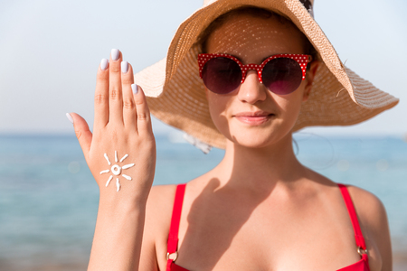 Young woman is showing her hand with sun shape made of sun cream at the beach.