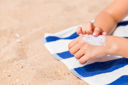 Girl is relaxing on the towel on the sand at the beach and applying sun lotion on her hand. Stock Photo