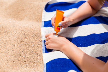 Attractive woman is lying on a striped towel at the beach and squeezing sunblock from a tube on her hand. Stock Photo