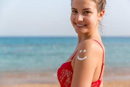 Gebräunte Frau hat Sonnencreme auf ihrer Schulter als lächelndes Gesicht gemacht.