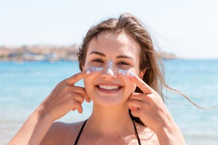 Mujer bronceada protege su rostro con crema solar de las quemaduras solares en la playa.