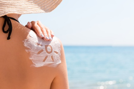 Sunscreen lotion in sun shape on tanned woman's shoulder.