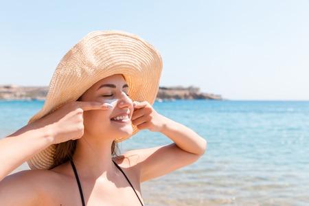 Hübsche Frau schützt ihre Haut im Gesicht mit Sonnencreme am Strand.