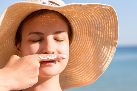 Cute woman is posing with moustache drawn with sun cream on her finger under her nose at the sea background.