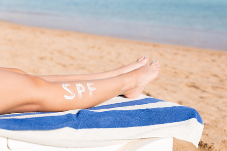 Female legs with spf word made of sun cream at the beach. Sun protection factor concept.