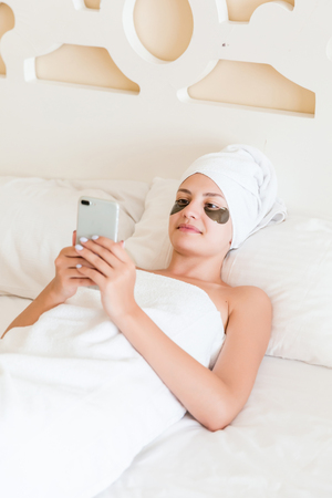 Beautiful young woman with under eye patches and using mobile phone in bathrobe lying in bed. Happy girl taking care of herself. Beauty skincare and wellness morning concept.