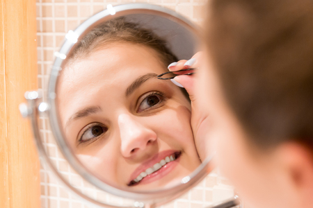 Beautiful woman with tweezers is plucking eyebrows while looking into the mirror in bathroom. Beauty skincare and wellness morning concept. Stock Photo