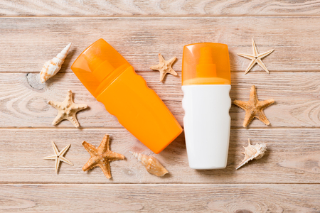 Sunscreen bottles with seashells and starfish on wooden table flat lay concept of summer travel vacation. 版權商用圖片
