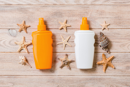 Sunscreen bottles with seashells and starfish on wooden table flat lay concept of summer travel vacation.