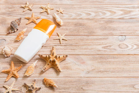 Sunscreen bottles with seashells and starfish on wooden table with copy space. flat lay concept of summer travel vacation.