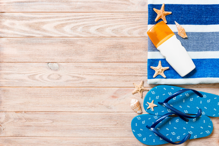 Top view of Beach flat lay accessories. sunscreen bottle with seashells, starfish, towel and flip-flop on wooden board background with copy space. Foto de archivo