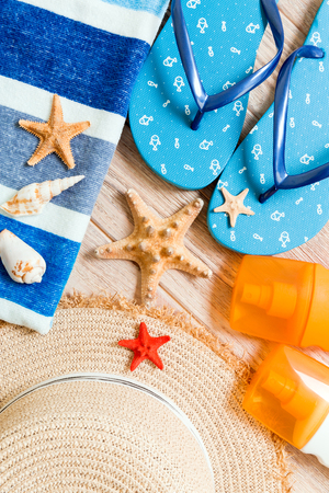 flip flops, straw hat, starfish, sunscreen bottle, body lotion spray on wooden background top view . flat lay summer beach sea accessories background, travel concept.