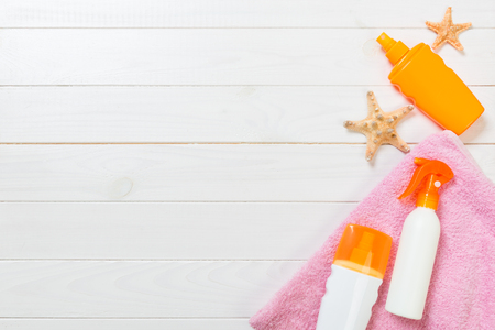 strandaccessoires op een witte houten achtergrond bovenaanzicht. Zonnebrandcrème, handdoek en seastar. Reizen gezondheidszorg accessoires bovenaanzicht.