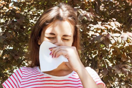 Young girl with allergy in autumn park. Sneezing girl blows her nose in a napkin.