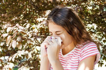 Young pretty girl blowing nose in front of tree. Spring allergy concept. Imagens