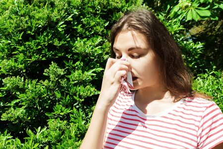 Woman with with allergy symptom blowing nose.